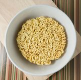 Asian Ramen or Instant Noodles in A Bowl. Cuisine and Food, Asian Ramen Dried Instant Noodles Blocks for Cooked or Soaked in Boiling Water in White Bowl Royalty Free Stock Photo