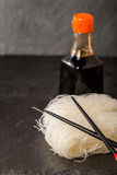 Asian raw glass noodles. Chopsticks and soy sauce on black background Stock Images