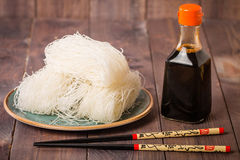 Asian raw glass noodles. Chopsticks and soy sauce on wooden background Stock Image