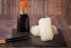 Asian raw glass noodles. Chopsticks and soy sauce on wooden background Royalty Free Stock Photos