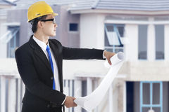 Asian real estate developer. Young asian businessman with blueprint inspecting the workplace Stock Photos