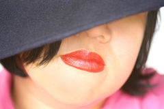 Asian red lips. Full red lips and an Ecuadorian navy blue wool hat partly covering face of young asian woman. Suited for cosmetic, fashion, anonymous, undercover royalty free stock photos