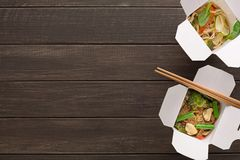 Asian food in delivery box on wooden backgorund. Asian restaurant food delivery. Funchoza with meat and vegetables. Vegetarian stir fry with noodles, broccoli Royalty Free Stock Photos