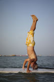 Asian Retiree doing a head stand on surf board Stock Photo