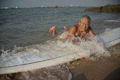 Asian retiree enjoying the waves on his surf board Royalty Free Stock Photography