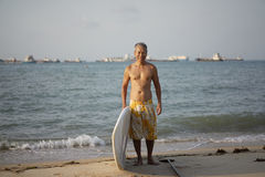 Asian Retiree posing with his surf board Royalty Free Stock Photo