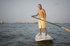 Asian Retiree on surf board Royalty Free Stock Images