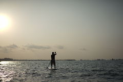 Asian Retiree on a surf up paddle against the sun Stock Images