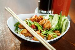 Asian riсe with chicken and vegetables in oval plate with bambo. O sticks on a wooden table in asian restaurant Stock Images