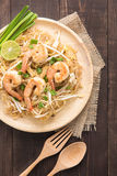 Asian rice noodles with shrimp and vegetables on wooden table. Royalty Free Stock Images
