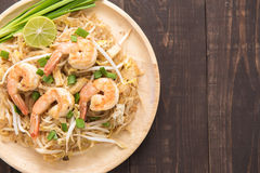Asian rice noodles with shrimp and vegetables on wooden table. Stock Images