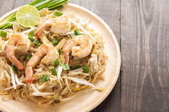 Asian rice noodles with shrimp and vegetables on wooden table. Stock Photo