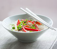Asian rice noodles with vegetables and sesame in a bowl on a linen textile background Stock Photos
