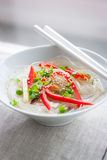 Asian rice noodles with vegetables and sesame in a bowl on a linen textile background Royalty Free Stock Photography