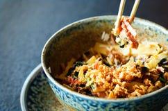 Asian rice with pork, Mu-err mushrooms, napa cabbage, pickled bamboo shoots, spinach, Teriyaki, sweet chili sauce, onion Stock Photo