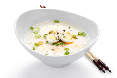 Asian Rice Porridge. Rice porridge, or jook with boiled quail eggs in white bowl with chopsticks on white background royalty free stock photography