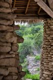 Asian stone village staircase. Asian rock pillars and grass roof overlooking green rock garden and staircase Stock Image