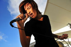 Asian Rock Star with microphone singing Royalty Free Stock Photos