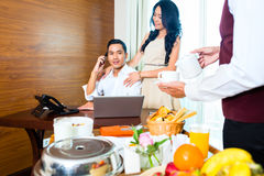 Asian room service waiter serving breakfast in hotel Stock Photo