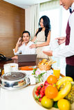 Asian room service waiter serving breakfast in hotel room Royalty Free Stock Photography