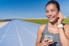 Asian runner listening to running motivation music. Asian runner woman listening to running motivation music with earbuds on her mobile phone app for run on royalty free stock photo