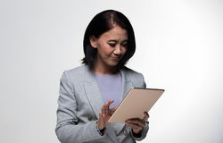 Asian 50s 60s years old Business Woman Stand suit. Asian 50s 60s years old Business Woman Stand in gray Formal Suit touch screen tablet, studio lighting grey royalty free stock photos