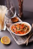 Asian salad with noodles and vegetables, sprinkled with sesame seeds with chopsticks on a wooden tray. Asian cuisine, garnish. Healthy food, vegetarian menu stock images