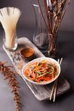 Asian salad with noodles and vegetables, sprinkled with sesame seeds with chopsticks on a wooden tray. Asian cuisine, garnish. Healthy food, vegetarian menu stock photography