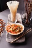 Asian salad with noodles and vegetables, sprinkled with sesame seeds with chopsticks on a wooden tray. Asian cuisine, garnish. Healthy food, vegetarian menu stock image