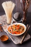 Asian salad with noodles and vegetables, sprinkled with sesame seeds with chopsticks on a wooden tray. Asian cuisine, garnish. Healthy food, vegetarian menu royalty free stock photography