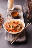 Asian salad with noodles and vegetables, sprinkled with sesame seeds with chopsticks on a wooden tray. Asian cuisine, garnish. Healthy food, vegetarian menu stock photos