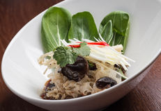 Asian salad, on white plate. Asian salad, pn white plate, wooden tabe Royalty Free Stock Images