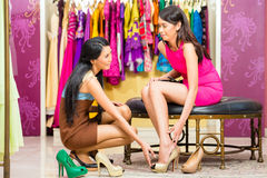 Asian sales lady in shop offering shoes. Asian young sales lady offering shoes to women in fashion store Stock Image