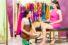 Asian sales lady in shop offering shoes Stock Photo