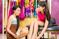 Asian sales lady in shop offering shoes Royalty Free Stock Photos