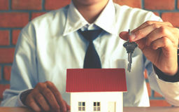 Asian salesman holding key and giving for customer with home con royalty free stock photography