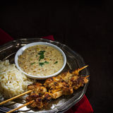 Asian satay chicken skewers with rice and peanut sauce on a silv Royalty Free Stock Photography
