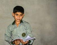 An Asian school boy holding a book. A Pakistani school boy holding a book Royalty Free Stock Photography