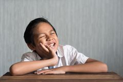 Asian school boy in pain holding his cheek because of toothache Royalty Free Stock Photography