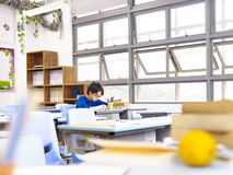 Asian school boy studying in classroom. Asian school boy studying alone in classroom Royalty Free Stock Photo