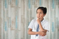 Asian school boy thinking while holding his chin royalty free stock image