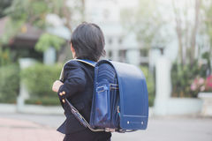 Asian school girl with pink backpack looking up Stock Image