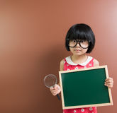 Asian school kid hold a chalkboard and magnifying glass Stock Photography
