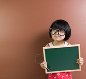 Asian school kid hold a chalkboard and magnifying glass Royalty Free Stock Images