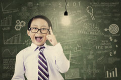 Asian schoolboy has an idea. With a light bulb at the classroom Royalty Free Stock Photography