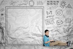 Asian schoolboy sits near drawn whiteboard. Closeup of an Asian preteen schoolboy using a laptop while sitting near drawn whiteboard. Shot with crumpled royalty free stock photography