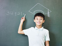 Asian schoolboy standing under a chalk-drawn doctoral hat. Asian elementary school boy standing under a doctorial hat drawn with chalk on blackboard stock photo