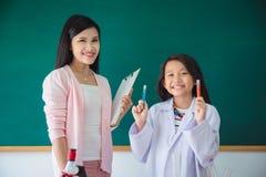 Schoolgirl and beautiful teacher standing in classroom. Asian schoolgirl and beautiful teacher standing in school classroom royalty free stock image