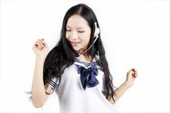 Asian schoolgirl enjoying music Stock Image