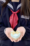 Asian schoolgirl holding a gift box Stock Images
